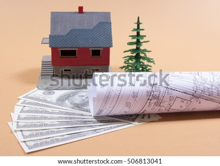 Many dollar banknotes and a house model.