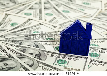 Many dollar banknotes and a house model; concept of buying a house - stock photo