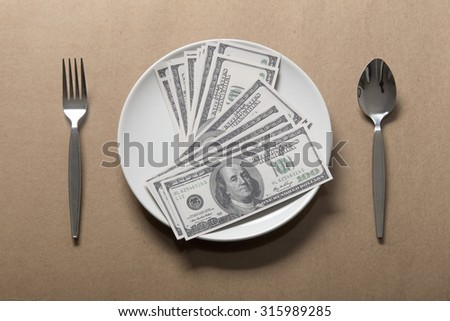 Many dollar on white dish with spoon and fork. - stock photo