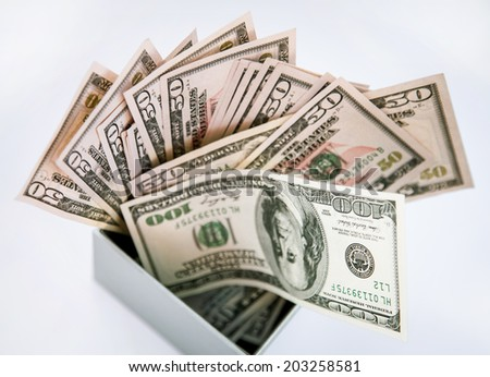 Many dollars banknotes in a grey box, closeup shot - stock photo