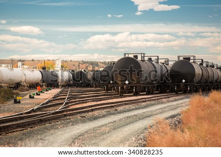 Many DOT-111 tank cars, commonly used in North America to transport crude oil to refineries along the coasts, parked in a rail yard at a refinery.