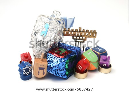Many Dreidals (tops), candle dreidals and small hannukia (Menorah or candelabra) grouped together against a white background
