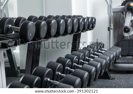 Many dumbbells are on stand at the gym