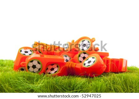 many Dutch soccer whistles in green field - stock photo