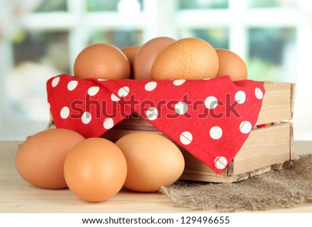 Many eggs in box on table in room - stock photo