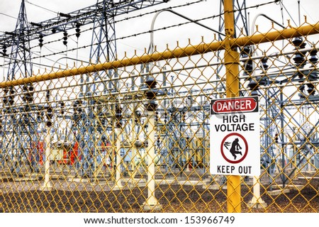 Many electrical substations have fences and warning signs to keep out. - stock photo