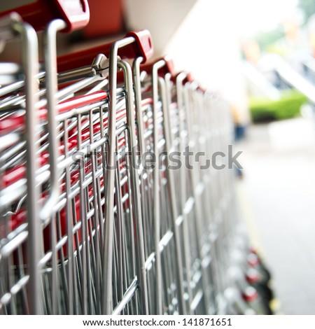 Many empty shopping carts in a row. - stock photo