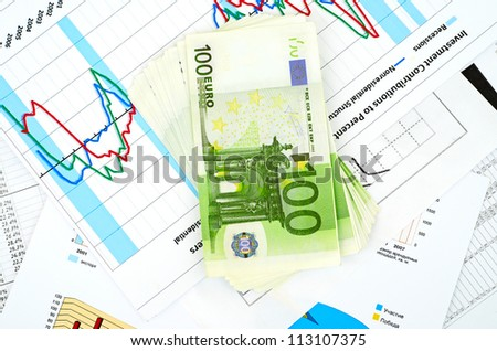 many euro bank notes and a compass lie side by side