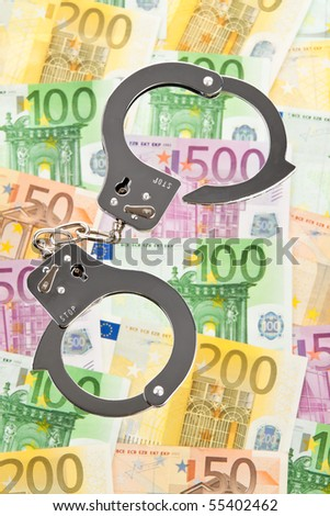 Many Euro bank notes with handcuffs - stock photo