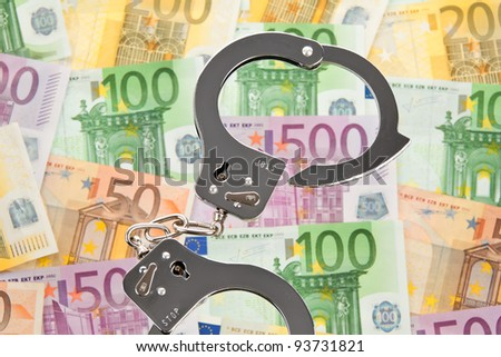 many euro bank notes with handcuffs. photo symbol-collar crime - stock photo