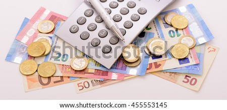 Many Euro banknotes and calculator laying on table