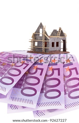 many euro banknotes and shell of a house - stock photo