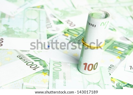 Many 100 Euro banknotes with some of them in a roll photographed standing. - stock photo