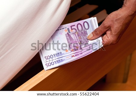 Many Euro notes are hidden under the bed. - stock photo