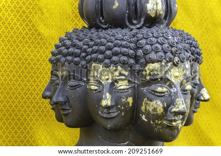 Many face of Buddha statue against golden background - stock photo