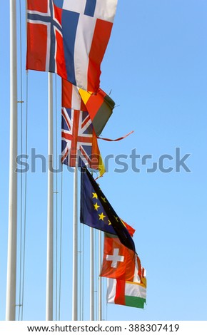 many flags of many nations in the wind on a sunny day with blue sky - stock photo