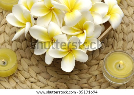 many frangipani in a wicker basket with two candle on mat - stock photo