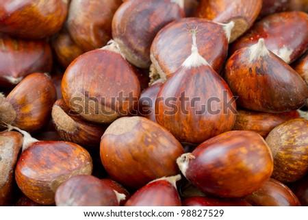 many fresh chestnuts as background - stock photo