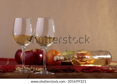 Many fresh ripe red apples and orange fruits with glassy bottle lying on checkered plaid near two goblets with white wine standing on wooden table top on paper background copyspace, horizontal picture - stock photo