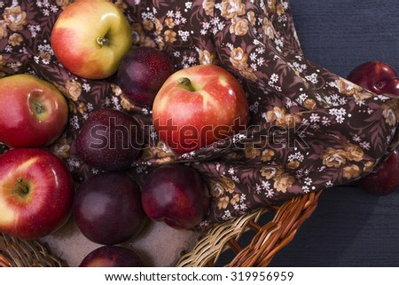 Many fresh tasty ripe clear fruits with vitamins of yellow red apple and purple plum lying in heap on brown fabric with floral pattern in straw basket on wooden background, horizontal picture - stock photo
