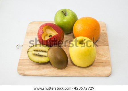 Many fruits Apples, orange, kiwi. Placed on a wooden cutting board