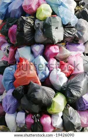 Many Garbage Plastic Bags With Different Colours Piled Up - stock photo
