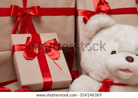 Many gifts, boxes with gifts covered with red satin and silk ribbon with big bow, merry Christmas and a happy new year, surprise, wishes, birthday or holiday a teddy bear - stock photo