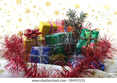 many gifts with colorful tinsel chain and pine branch lie on a light fabric