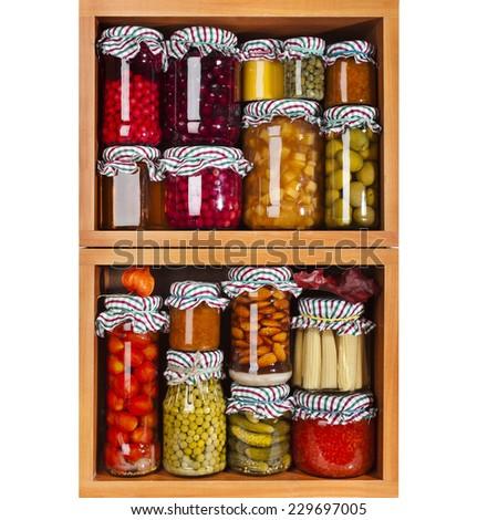 many glass bottles with preserved set food in wooden cabinet - stock photo