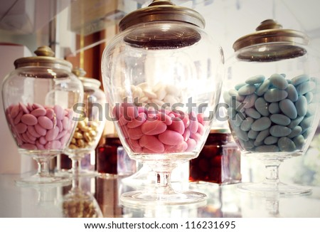Many glass containers with different colors of sugared almond - stock photo