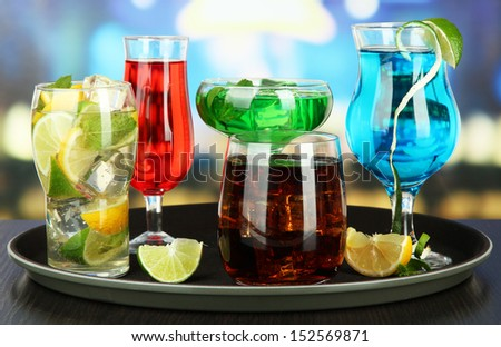 Many glasses of cocktails on tray on table, on bright background - stock photo