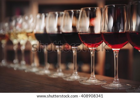Many glasses of different wine in a row on bar counter - stock photo