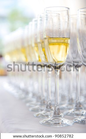 Many glasses with champagne in a line - stock photo