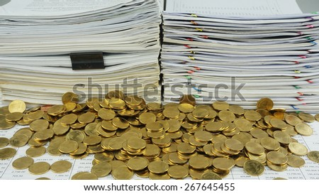 Many gold coins was put together in front of a pile of old documents.                                - stock photo