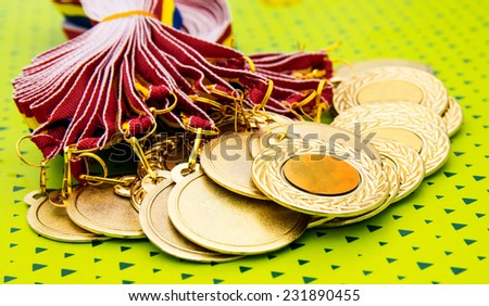 Many gold medals waiting for the winners on a green background - stock photo