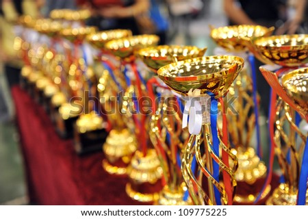 Many gold trophies in a row. - stock photo