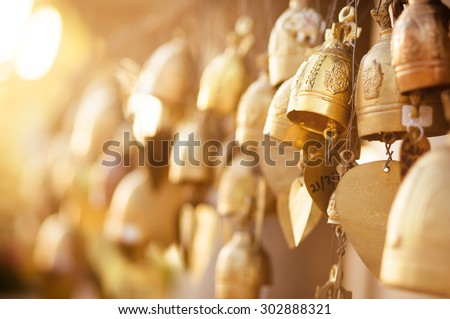 Many golden buddhist bells with wishes in sunlight - stock photo