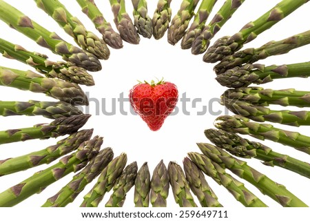 Many green asparagus spears arranged to a circle. Tips pointing inwards to a heart-shaped strawberry in the center. Cutout isolated on white. Selective focus on the fruit and front half of the ring. - stock photo