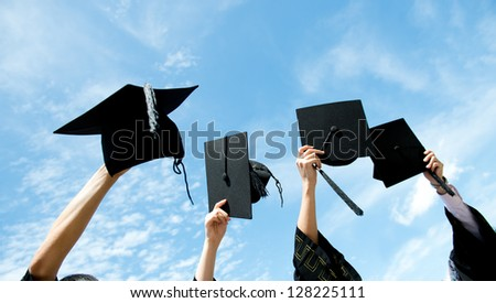 Many hand holding graduation hats on background of blue sky. - stock photo