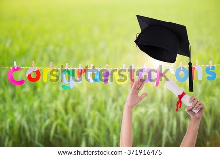 Many hand holding graduation hats on background of Green pastures. And the message, Congratulations! - stock photo