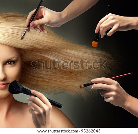 many hands applying make up on a woman face - stock photo