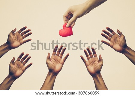 Many hands chasing, fighting to get a red heart - fighting for love concept - stock photo