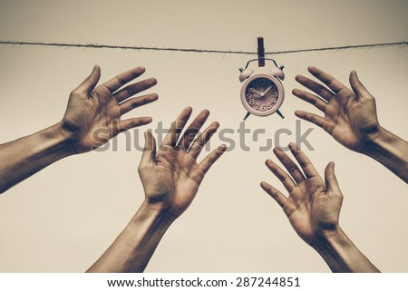 Many hands competing against one another to reach a clock hung on a rope - Time waits for no man  - stock photo