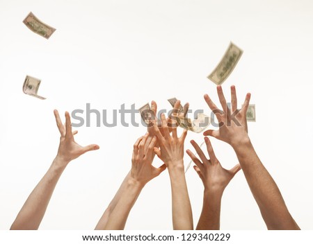 Many hands competing for catching money falling from above, white background - stock photo