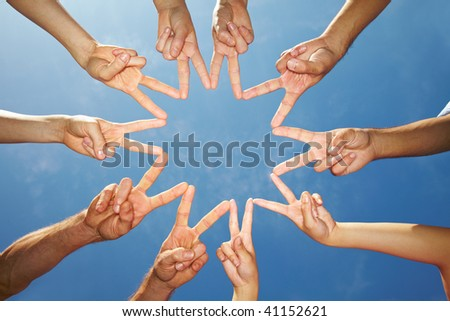 Many hands connecting to star shape under sky