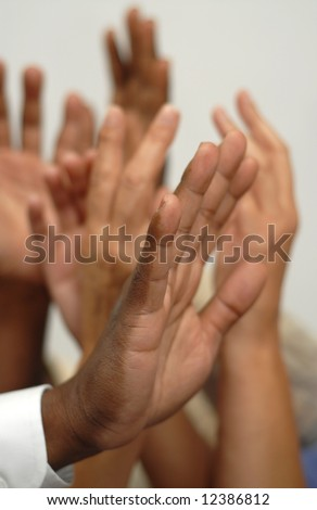 Many hands going up either in a question or during an election - stock photo