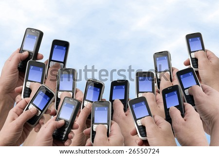 Many hands holding mobile phones with empty text message boxes - stock photo