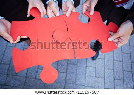 Many hands holding two red jigsaw puzzle pieces - stock photo