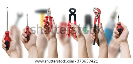 Many hands holds up instruments and tools on blurry background. Maintenance concept. - stock photo
