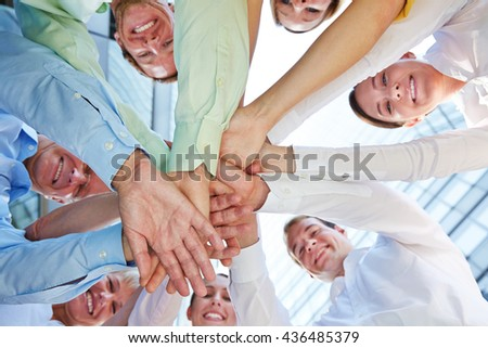 Many hands of business people stacked as symbol for teamwork